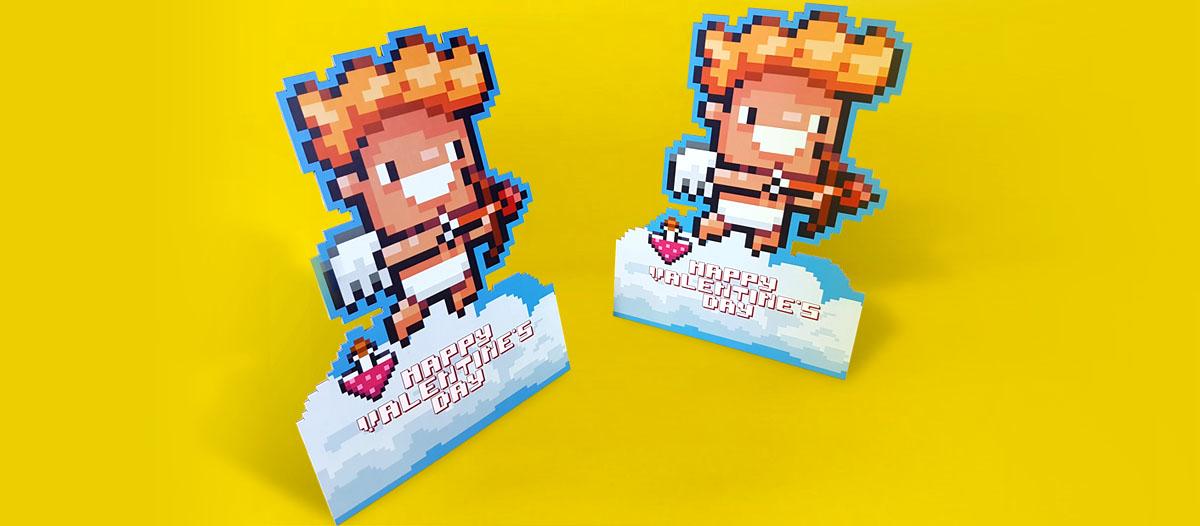 Display publicitario, realizado en cartón compacto, con un diseño de un Cupido que está lanzando una flecha y que tiene una pócima del amor. Es una imagen pixelada que simula la apariencia de un videojuego.