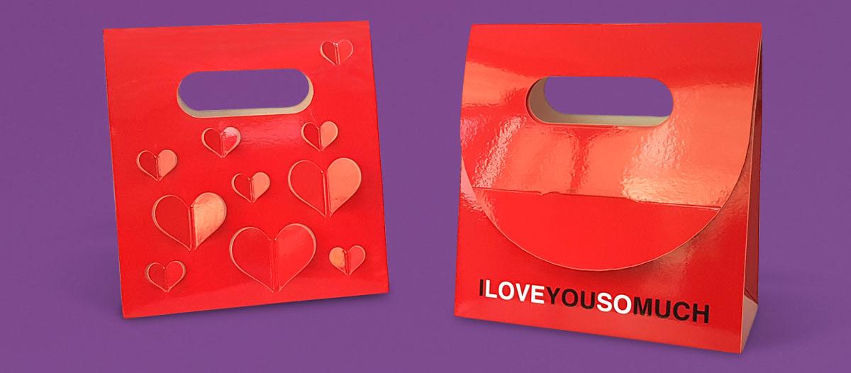 Un caja tipo bolsa en color rojo con un diseño creativo para San Valentín: por un lado, corazones troquelados y, por el otro, el mensaje I love you so much.