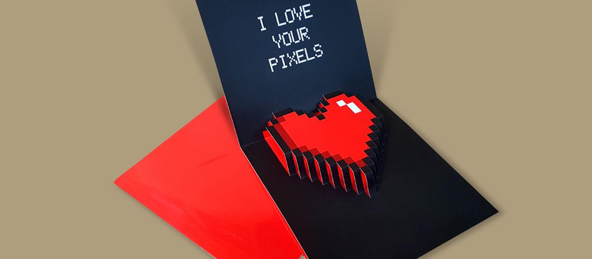 Tarjeta pop up para felicitar el Día de San Valentín. Con un diseño de un corazón troquelado, como si estuviera hecho con pixeles que se despliega cuando se abre la tarjeta