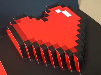 Una tarjeta de felicitación pop up para el Día de San Valentín que tiene un diseño de un corazón troquelado a modo de pixel