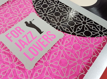 Una original funda de disco de vinilo impresa sobre papel plateado y con detalles en tinta rosa fluorescente