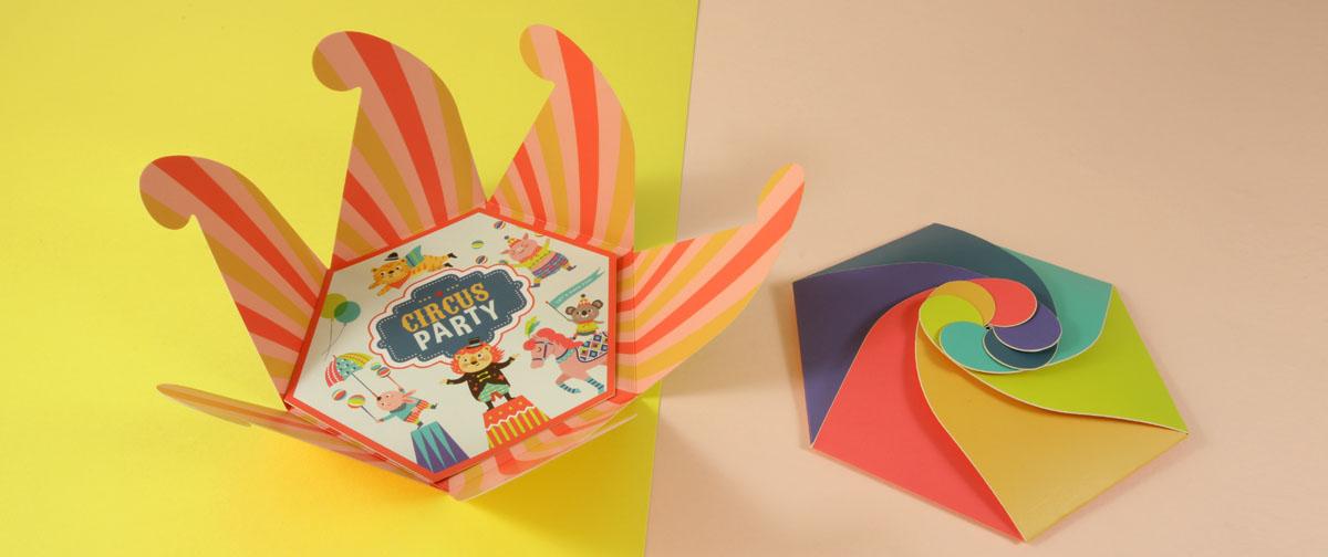 Invitación con caja multicolor. Tiene un cierre en espiral que simula ser una capa de un circo, diseñada para una fiesta infantil Circus Party - Truyol Digital