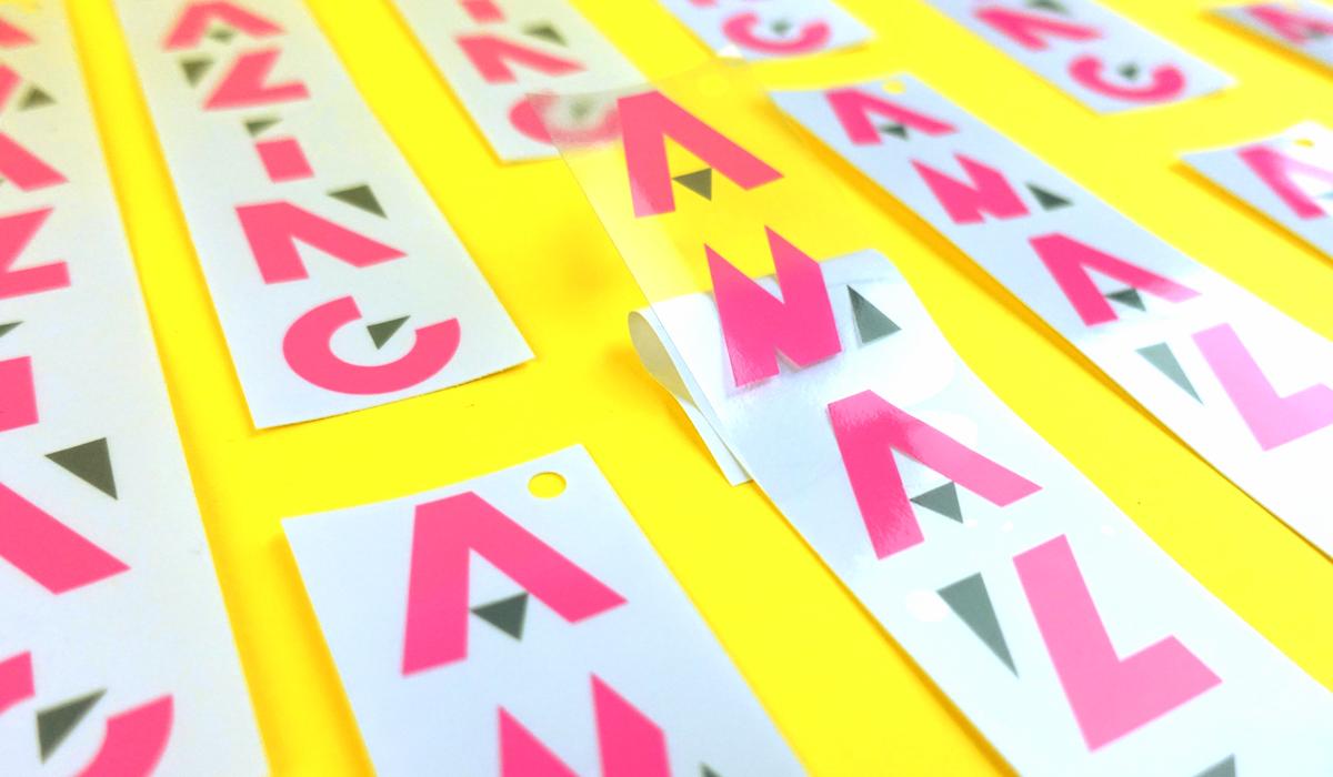 Pegatina impresa con tinta rosa flúor sobre adhesivo de PVC transparente. Se ha aplicado tinta blanca para opacar la impresión.